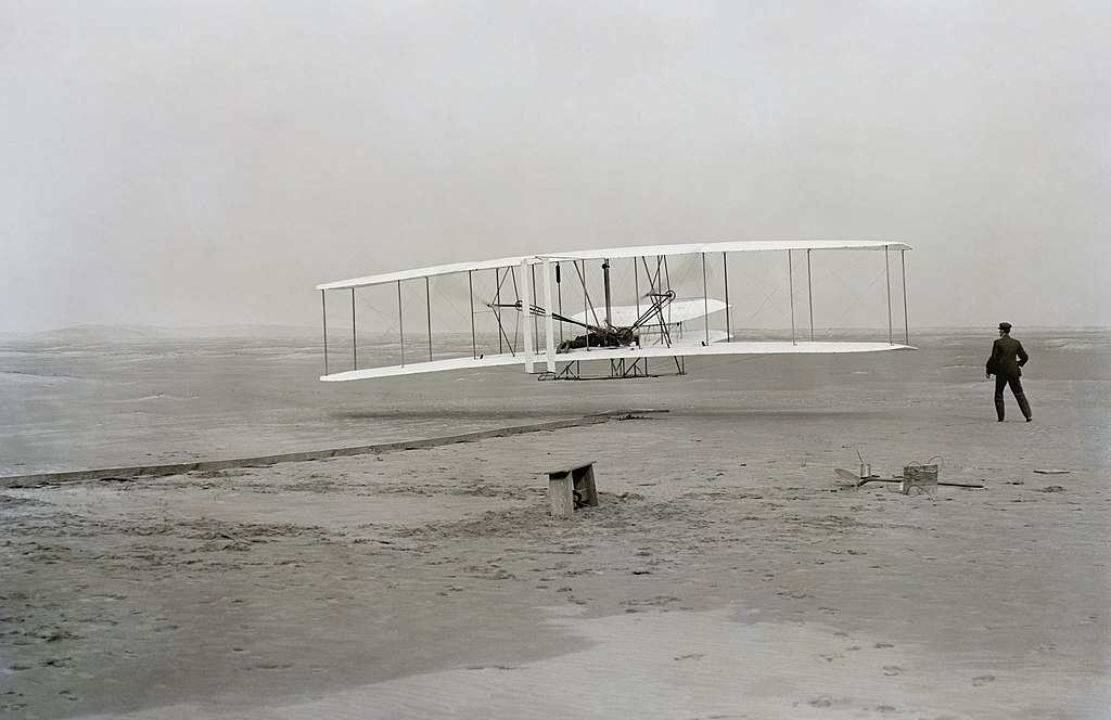 Orville Wright flies an aircraft with a petrol engine at Kitty Hawk, North Carolina, in the first documented, successful, controlled, powered, heavier-than-air flight